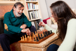 elderly man and caregiver playing chess