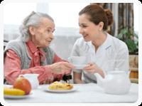 caretaker preparing meal for her patient